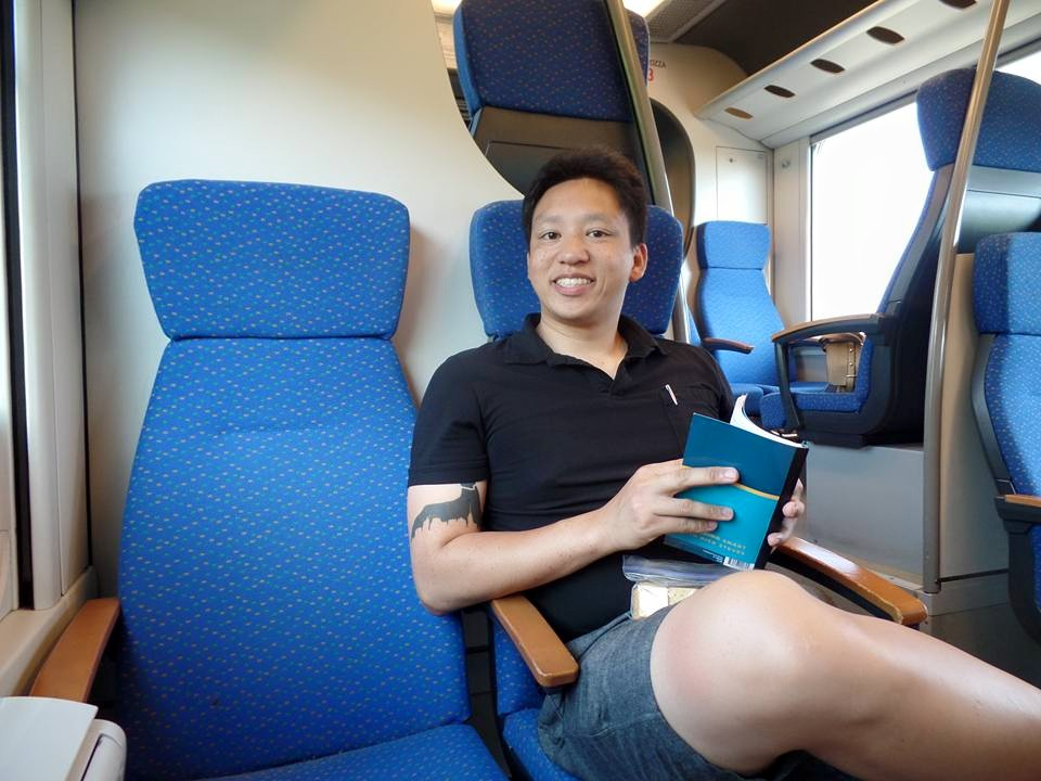 Riding the Malpensa Express Train to Milan! He's all ready with our Rick Steves guide book.